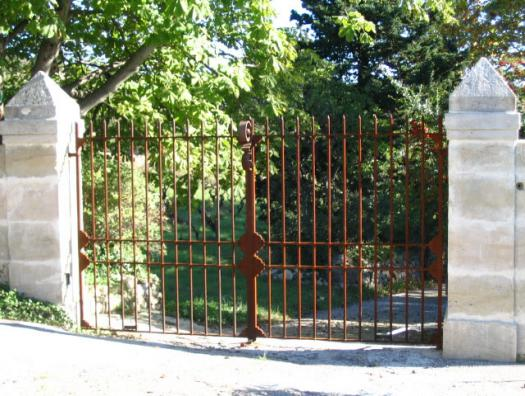 Portail barreaudé, qui offre aux passants le spectacle végétal du jardin
